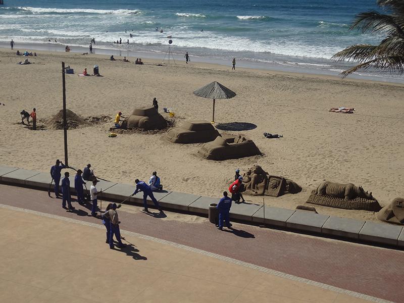 Ik tel acht werkmensen die dit stukje zand moeten opkuisen. Eén is aan het werk. Lang leve de werkgelegenheid! [Getrokken in Durban]