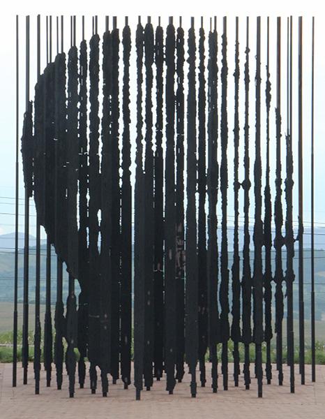 Het Mandela Monument in Howick bestaat uit tientallen ijzeren palen die voor en achter elkaar staan. Je krijgt het portret van Mandela enkel te zien als je op exact de juiste plek gaat staan.
